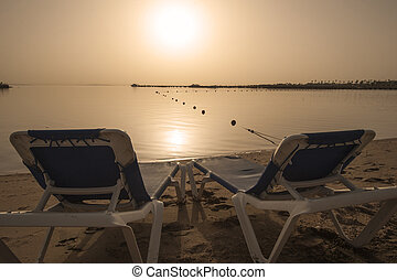 Sun loungers on tropical beach at sunrise