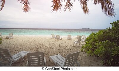 Sun Loungers on Tropical White Sand Beach in the Maldives -...