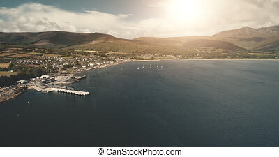 Sun ocean bay at port town aerial at nobody nature seascape. Ship, yachts, boats on coast of Atlantic gulf. Rural cityscape with houses, cottages, roads. Brodick town, Arran Island, Scotland, Europe