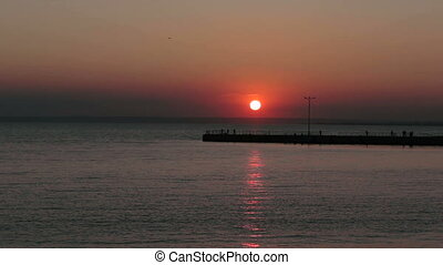 Sun over the water and wharf FullHD