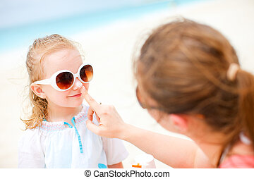 Sun protection - Mother applying sunblock cream on her...