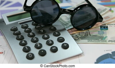 Sun protective hipster glasses lie on the calculator and...
