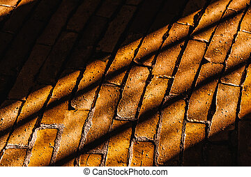 Sun rays and shadows in the brick road