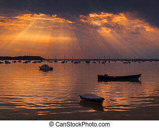 Sun rays illuminate boats in Poole Harbour