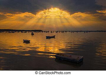 Sun rays illuminate boats in Poole Harbour