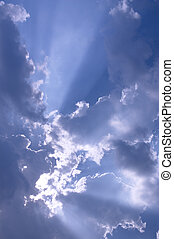 Sun rays bursting from behind white clouds and blue skies