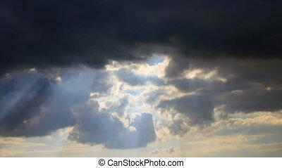 Sun rays through dark grey clouds