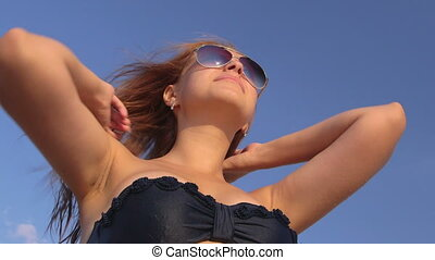 Sun reflection in sunglasses of young girl on the beach