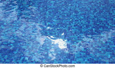 """Sun reflection sparkle, blue water surface, hotel swimming pool"""