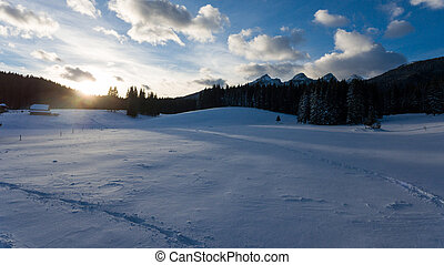 Sun rising above snow covered meadow.