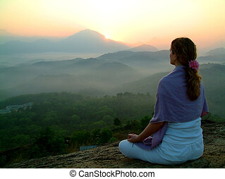 woman meditating during sunrise, neyyar dam, india