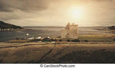 Sun seascape at castle ruins aerial. Ocean coast with yachts, ships. Historic heritage landmark. Nobody nature landscape. Tourist attraction. Loch-Ranza Bay, Arran island, Scotland, Europe at sunlight