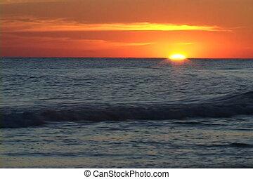 Sun Set On Horizon - Sun sets on the horizon with waves...