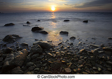 sun set on sea scape with natural rock foreground
