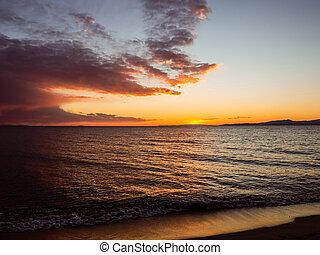 Sun set over the horizon - beautiful empty beach - small waves