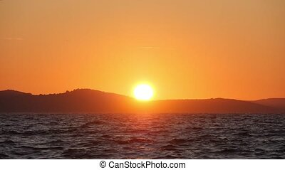 Sun sets into the sea. Waves and splashes shine in sunset light. Bright colors