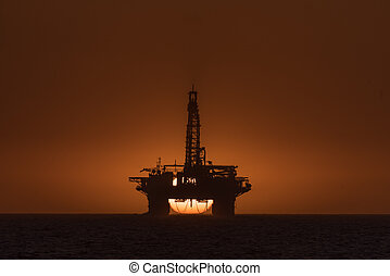 Sun setting behind oil drilling platform at Longbeach in Namibia