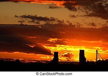 Sun setting behind two Saskatchewan grain elevators