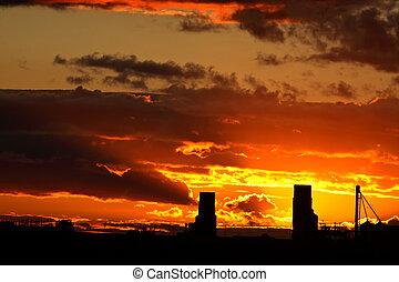 Sun setting behind two Saskatchewan grain elevators