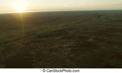 Sun setting in dessert - A shot from inside a plane that is...