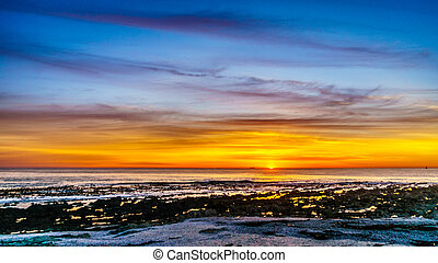 Sun setting under orange sky over the horizon of the Atlantic Ocean at Camps Bay