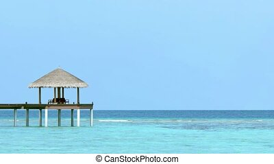 Sun shelter, with thatched roof, stands on the end of a pier, overlooking the Indian Ocean from a resort in the Maldives. 4k video