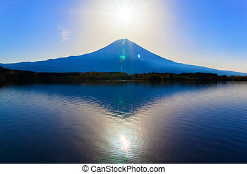 Sun shine and inverted Mount Fuji reflected in Lake Tanukiko