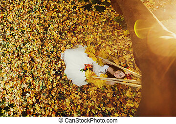 Sun shines over a bride which sits in a wreath on the swing