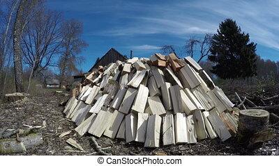 Sun shining on big heap of cut firewood, time lapse 4K - Sun...