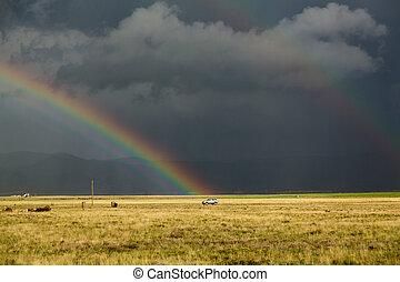 Sun shining on grassland under storym and rain