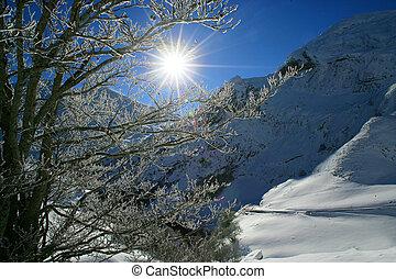 Sun shining onto snow covered mountain