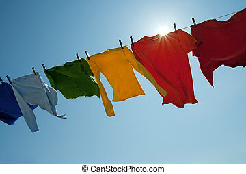 Sun shining over a laundry line with bright clothes