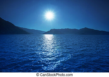sun shining over blue water of fresh water lake and mountain bac