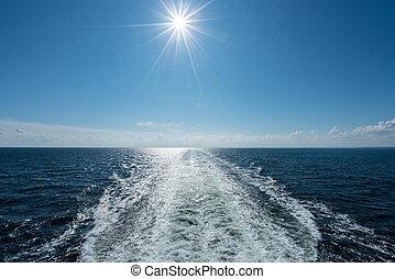 Sun shining over the wake of cruise ship at sea