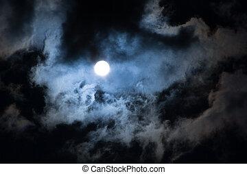 Sun shining through dramatic clouds, looks like a Moon.