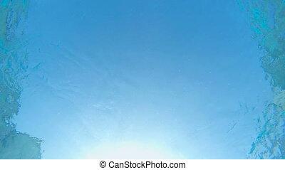 Sun shining through the blue water of swimming pool underwater shot