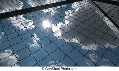 Sun shining through the chain link iron wire fencing