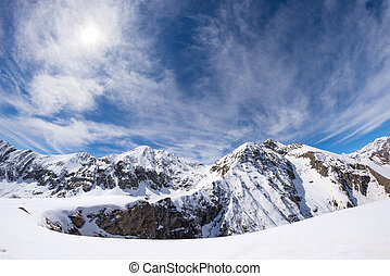 Sun star glowing over snowcapped mountain range and high mountain peaks in the italian alpine arc, in a bright sunny day of winter. Candid snowy slope in the foreground.