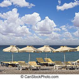 sun umbrella and chairs on a beach