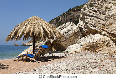 sun umbrella and chairs on a rock beach