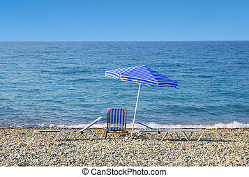 Sun umbrella and sunbeds in front of a blue sea and sky