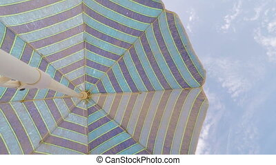 Sun umbrella for the sun, on a background of blue sky.