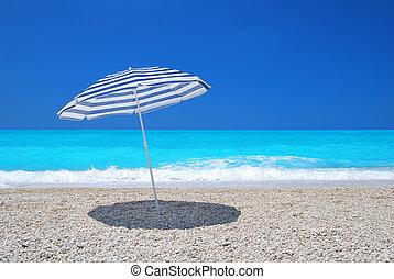 Sun umbrella on a pebble beach with turquoise sea and sky