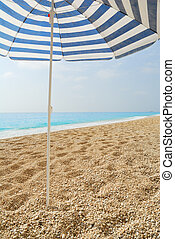 Sun umbrella stuck in a pebble beach with blue sea