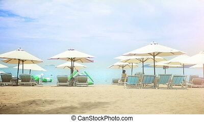 Sun umbrellas and chairs on a sandy beach.
