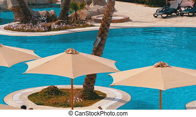 Sun Umbrellas by the Pool with Blue Water in the Hotel of Egypt