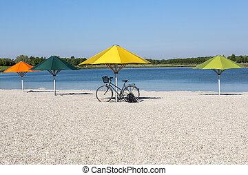 Sun umbrellas on a bathing lake in Munich, Bavaria