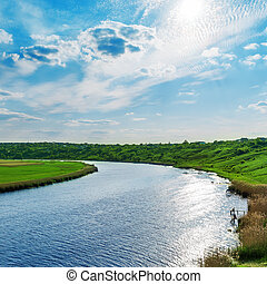 sun with clouds in blue sky over river
