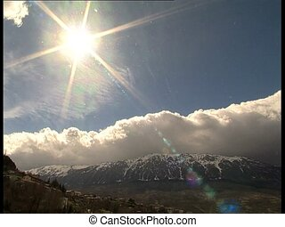 SUN with mountains and clouds - Shiny sun over the...
