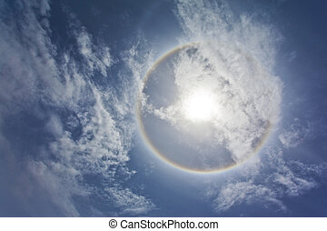 Sun with sircular rainbow and clouds